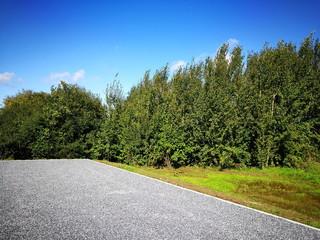 Parkplatz mit grauem Schotter vor grüner Landschaft mit blauem Himmel in Oelde bei Rheda-Wiedenbrück in Westfalen