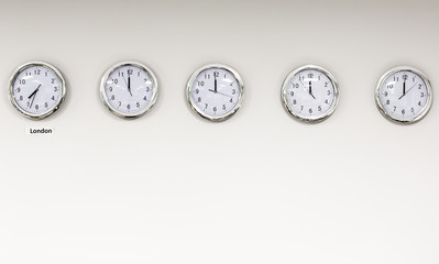 Modern quarz analog clocks on white wall in office