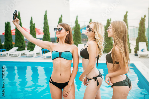 35ee67a3a3 Three happy girls makes selfie near the pool