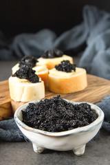 Sandwich with caviar of black sturgeon and white bread. Dark background.