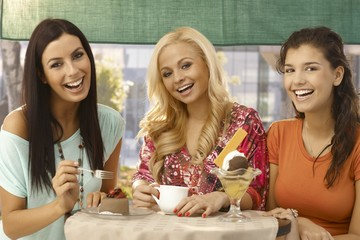 Pretty female friends by cafe table smiling