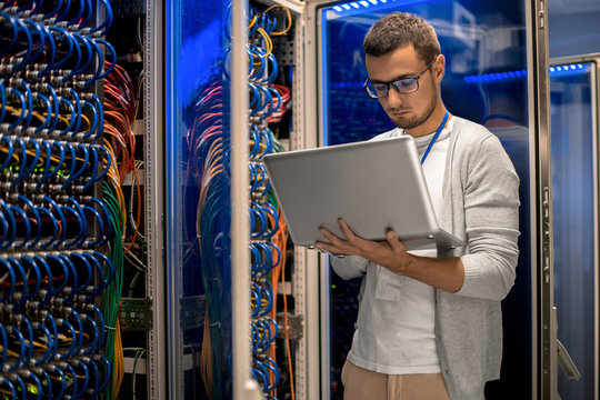 Portrait of modern young man holding laptop standing in server room working with supercomputer in blue light