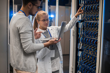 Portrait of young man and woman standing by server cabinets and discussing data while working with supercomputer in IT center