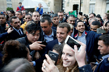 French President Emmanuel Macron poses for a selfie with a visitor in the Elysee Palace in Paris