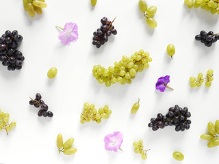 Black and green grapes, lilac flowers on a white background. The pattern of grapes of different varieties, top view. Food background.