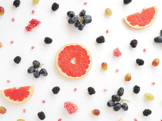Fototapete - Concept of healthy food. Berries and fruit pattern. Slices of grapefruit, blackberries, grains of pomegranate, black and green grapes on a white background.Composition of berries and fruits, top view.
