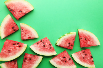 Slices of watermelons on green background