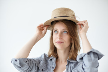 People, clothing, design, style, fashion and shopping concept. Isolated studio picture of gorgeous blue-eyed young woman with freckles trying on vintage round hat while shopping at flea market