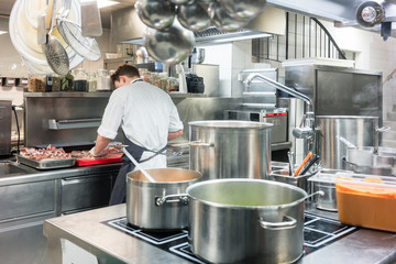 Rear view of a master chef preparing red meat on the counter of a commercial kitchen