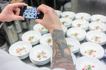 Chef photographing savory dish with a mobile phone for advertising catering services
