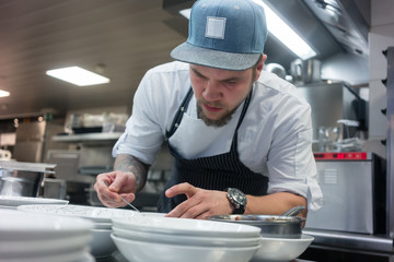 Young dedicated master chef plating high quality food in the kitchen of an exclusive restaurant