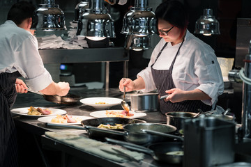 Dedicated young woman styling savory dish while working as a cook in an exclusive restaurant