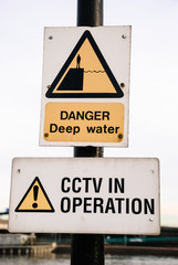 Signs at a harbour warning about deep water, and that CCTV is in operation