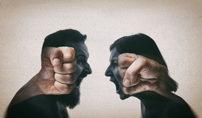 Double exposure image. A man and a woman scream at each other, their silhouettes are combined with a picture of fists to enhance drama.