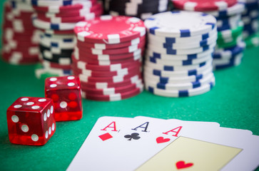three aces and red cubes with poker chips on green table