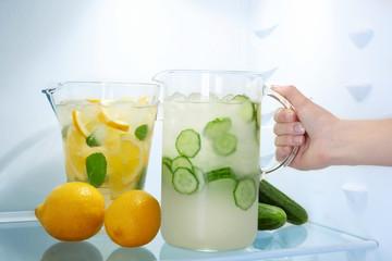 Female hand taking jug of cucumber lemonade from fridge