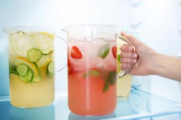 Woman taking jug of strawberry lemonade from fridge