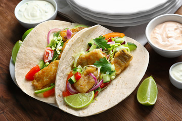 Plate with tasty fish tacos and sauces on wooden table