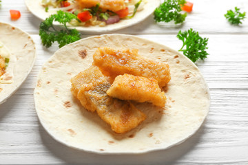 Tasty taco with fried fish fillet on wooden table