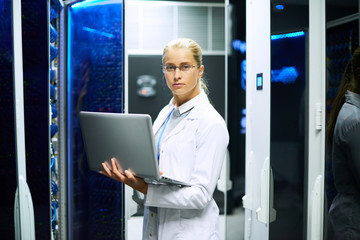 Portrait of young woman wearing lab coat working with supercomputer standing in server room holding laptop
