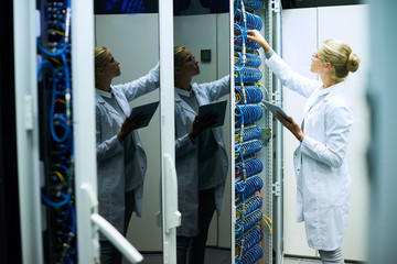 Young woman wearing lab coat working with server cluster in supercomputer research center