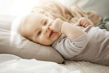 Portrait of sweet smiling newborn daughter lying on cozy bed. Child looks at camera and touching face with her little hands. Childhood moments.