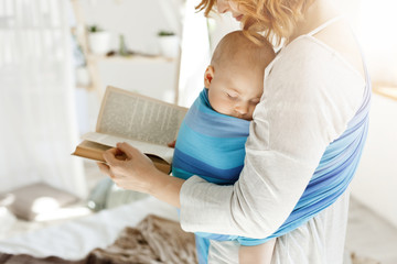 Close up of young mom reading fairy tales for her newborn little son in comfortable light bedroom. Baby falls asleep while she was reading.