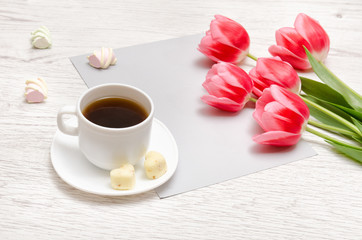 Pink tulips on a blank sheet of paper, mug of coffee and marshmallows, light wooden background