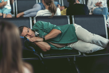 Jaded adult man is resting on seat at departure room