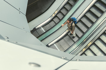 Young male traveler is standing on moving staircase