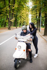 Young love Couple with scooter looking at map.