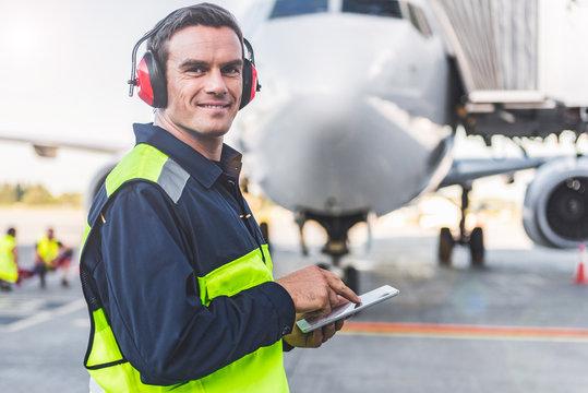 Happy mechanic having job in airdrome