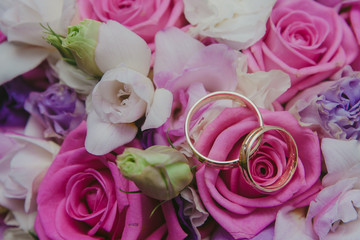 Golden wedding rings on flowers bouqet made of white and pink roses.