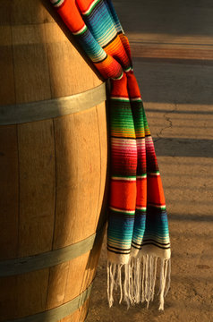 decorative Mexican woven blanket with brilliant colorful stripes hanging over wooden barrel