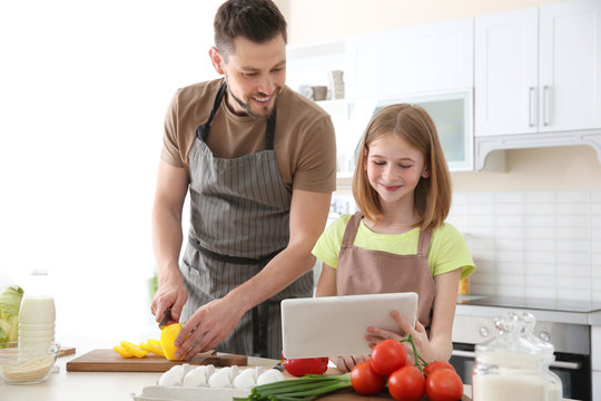 Father and daughter making meal together in kitchen. Cooking classes concept