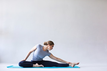 Young beautiful woman in sportswear doing stretching while sitting on the floor on yoga mat.