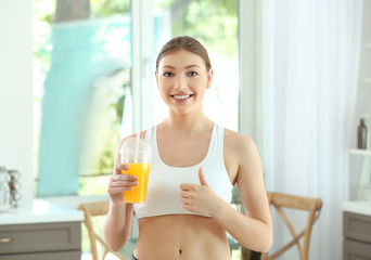 Beautiful young woman with juice at home. Diet concept