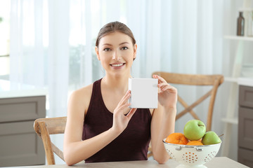 Beautiful young woman with biologically active supplement sitting at table. Diet concept