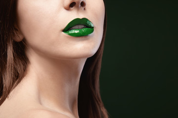 Young beautiful woman with fancy green lipstick on dark background, closeup