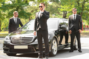 Handsome bodyguards near car outdoors