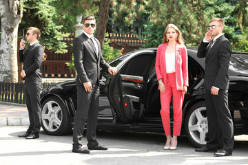 Famous celebrity with bodyguards near car outdoors