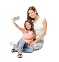 Cute little girl with mother taking selfie on white background