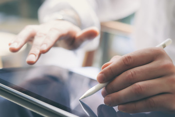Closeup view of male hands holding digital tablet on hand and using electronic pen while working at sunny office.Stylus pointing tablet screen.Blurred background.Horizontal.