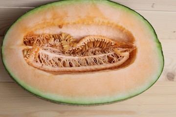 Half cantaloupe melon with seeds on wood background