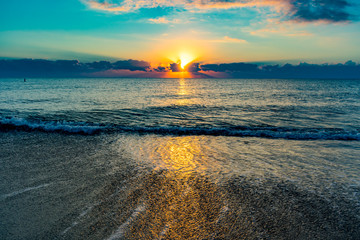 blue and yellow sky over calm ocean waters on a warm summer morning at sunrise