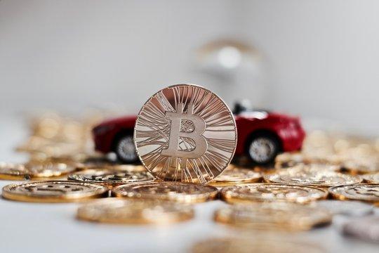 Bitcoin coin near red car