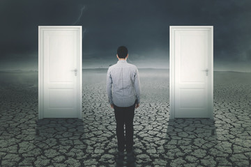 Young man standing with two doors