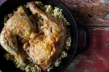 roasted chicken thighs over rice in cast iron pan closeup top view