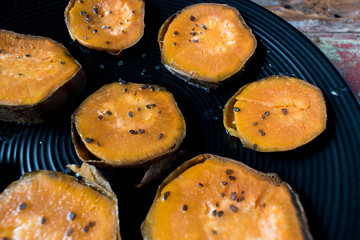 sliced sweet potatoes on black plate closeup