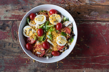 garden salad with tomatoes, cheese, and eggs rustic top view